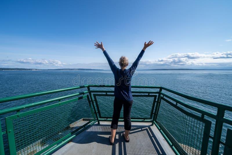 Kvinnapassageraren på porten Townsend Ferry i Washington State står med hennes armar upp och tillbaka till kameran, som fartyget  royaltyfria foton