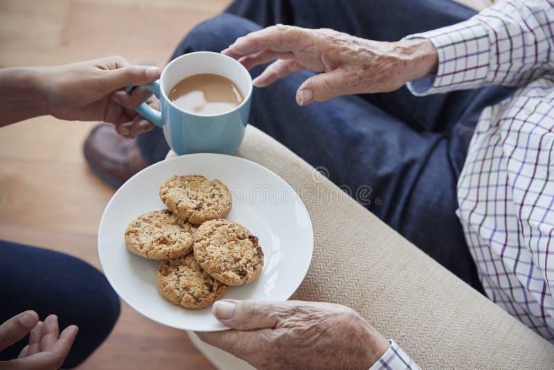 Kvinnapasserande te och kex till en placerad hög man, detalj royaltyfri bild