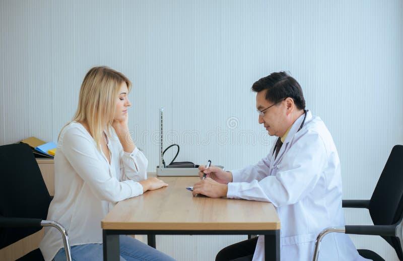 Kvinnapatient som talar med doktorn för höga män som undersöker och att följa upp behandling på sjukhussalen, deprimerad kv royaltyfri foto