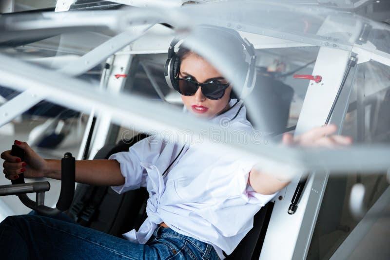Kvinnapilot i hörlurar med mikrofonsammanträde i liten nivå royaltyfri bild