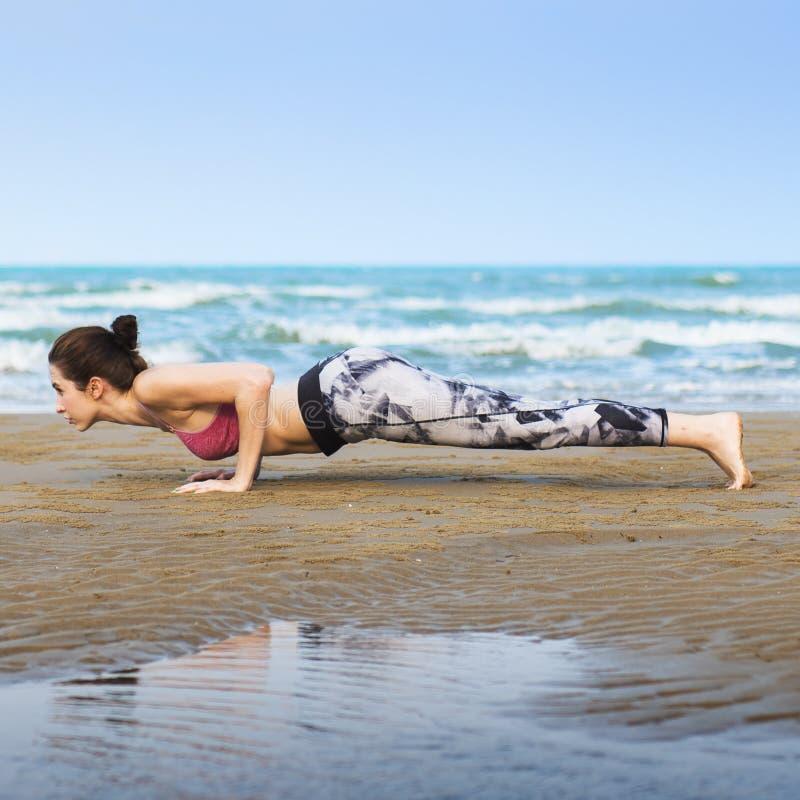 Kvinnaplank som sträcker det Flex Training Healthy Lifestyle Beach begreppet royaltyfri foto