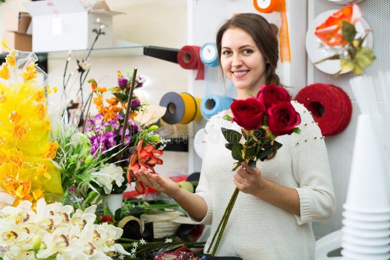 Kvinnaportion som väljer blommor arkivfoton