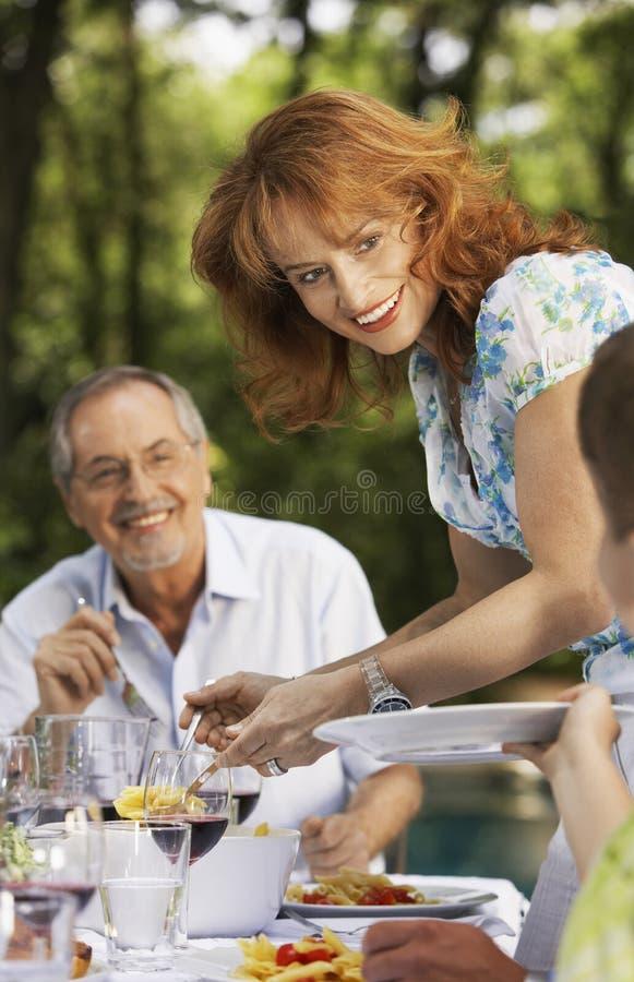 Kvinnaportionmat på familjen på tabellen arkivfoto