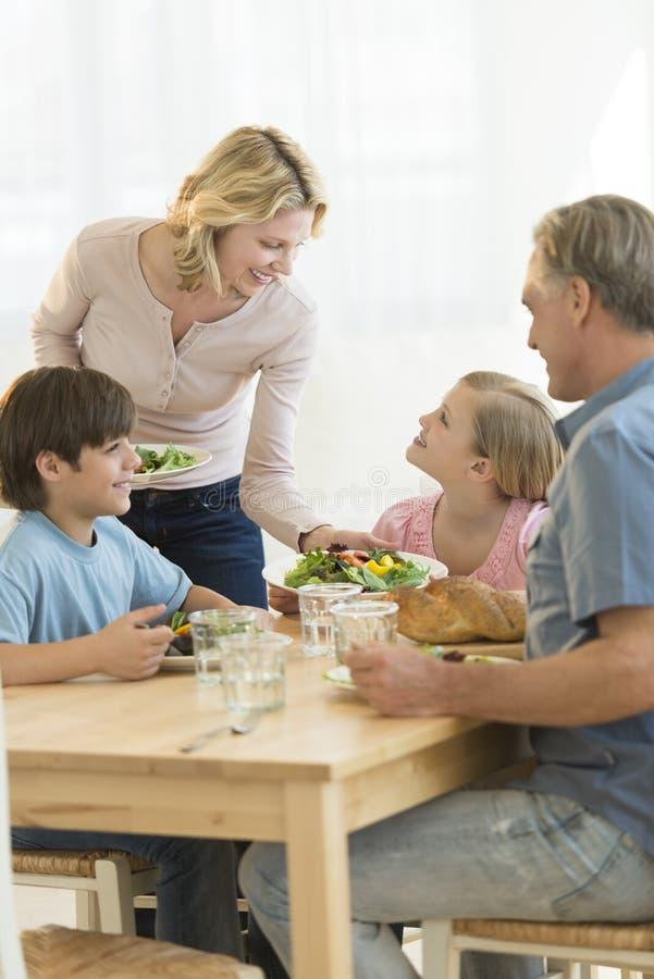 Kvinnaportionmat till dottern på att äta middag tabellen arkivbild