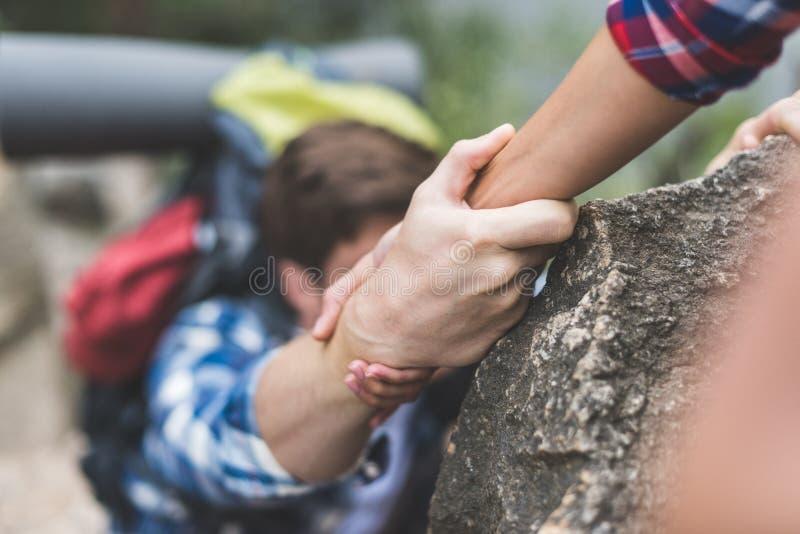 kvinnaportionpojkvännen som ska klättras, vaggar royaltyfria foton