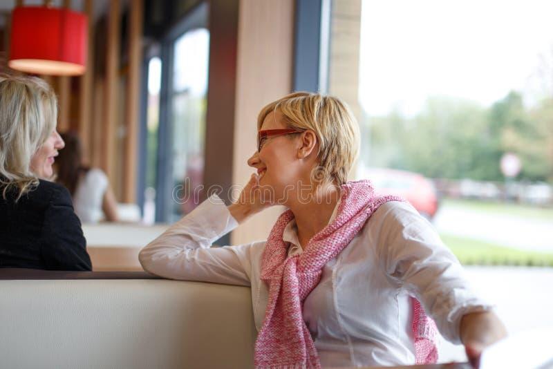 Kvinnapratstund i restaurang royaltyfri fotografi