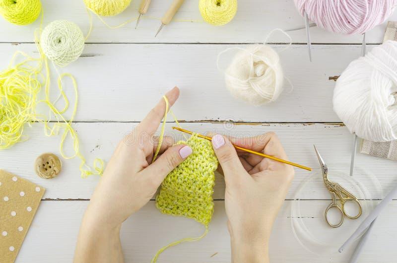 Kvinnarät maskakläder Vitt skrivbord för bästa sikt med hjälpmedel och stickatillbehör Kvinnors händer rymmer stickor arkivbild