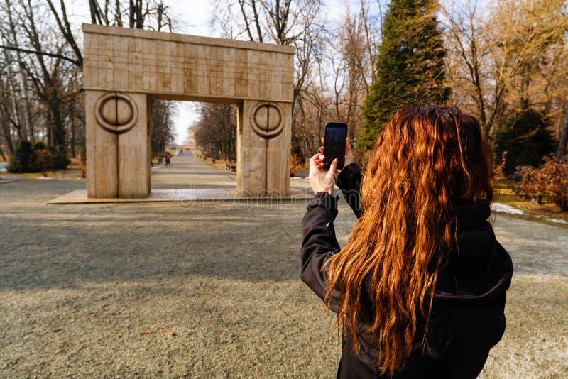 kvinnaresande till och med Rumänien Targu Jiu, kyssande port arkivfoton