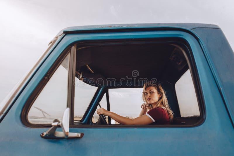 Kvinnaresande vid en bil på vägtur arkivfoton