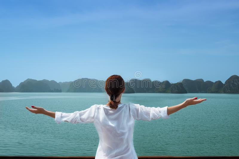 Kvinnaresanden med fartyget bland öarna med armar up känslig fri salighet royaltyfria bilder