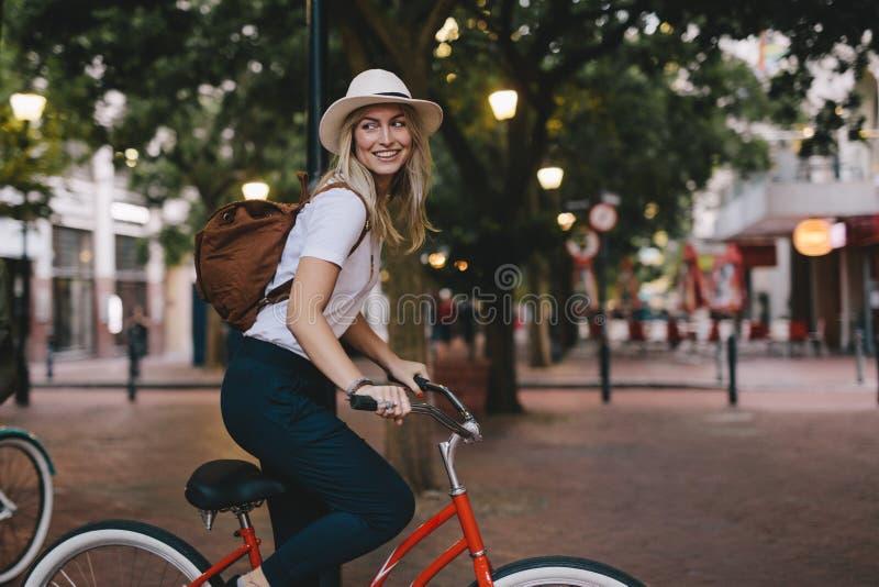 Kvinnaridningcykel i stad royaltyfri bild