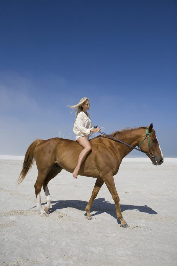 Kvinnaridninghäst på stranden fotografering för bildbyråer