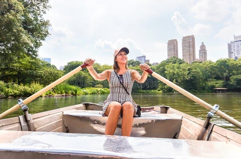 Kvinnarodd en roddbåt och en hagyckel i natur Rodd i sommar Le den lyckliga damen som tycker om utomhus- aktivitet arkivfoto