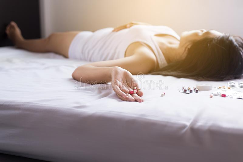 Kvinnasömn som är medvetslös efter äten preventivpiller, drogpreventivpilleren och knarkaren överdoserar begrepp royaltyfri fotografi