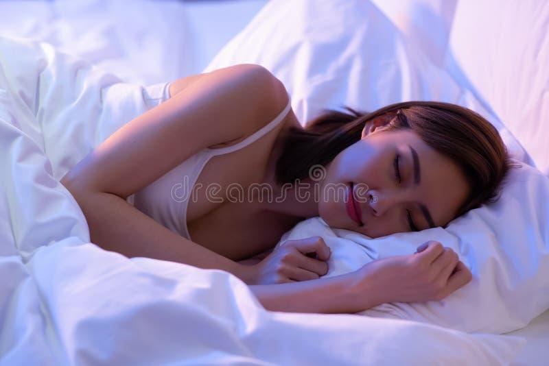 Kvinnasömn väl på säng royaltyfria foton