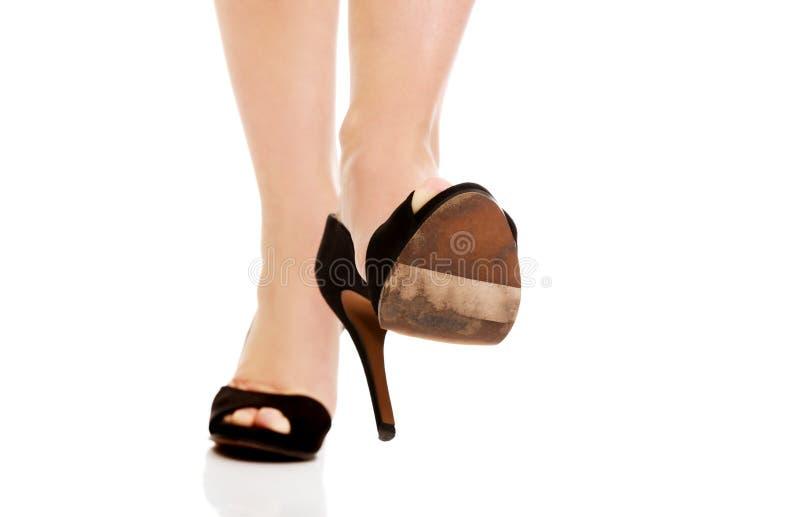 Kvinnas ben i höga häl som försöker att trampa något royaltyfria foton