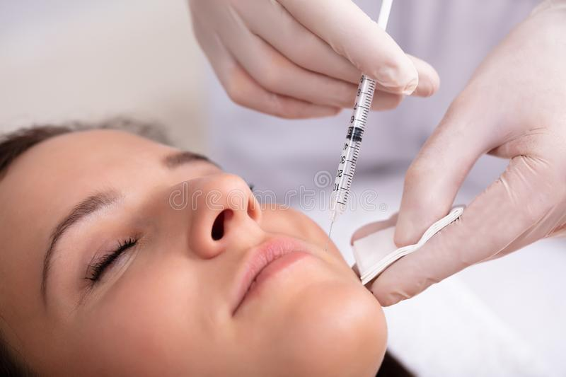 Kvinnas f?r doktor Giving Injection On framsida royaltyfri fotografi