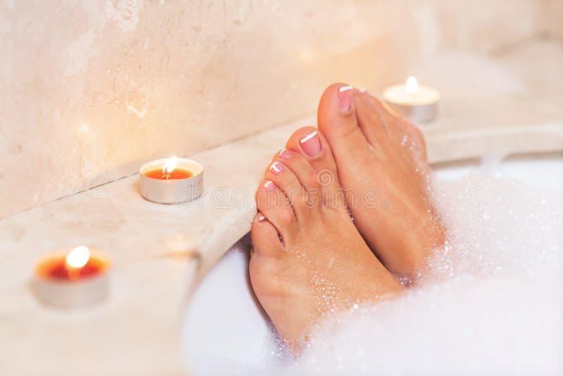 Kvinnas fot i badskum Avkoppling i hotell eller brunnsort royaltyfri foto