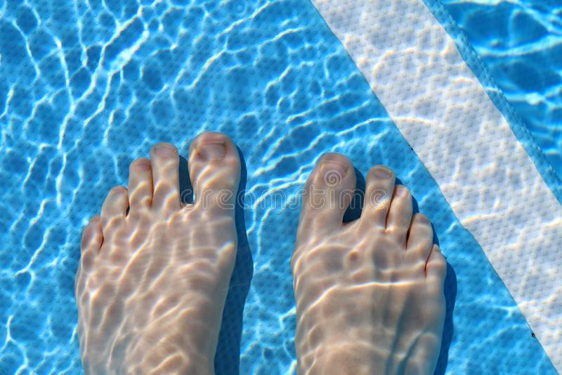 Kvinnas fot i grunt pölvatten under en Sunny Day royaltyfri bild