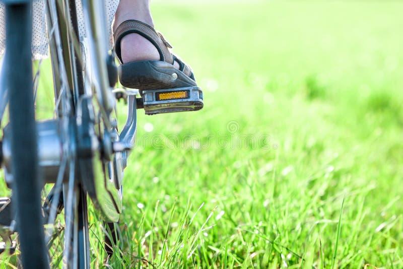 Kvinnas fot på cykelpedalen på closeupen för grönt gräs arkivfoton