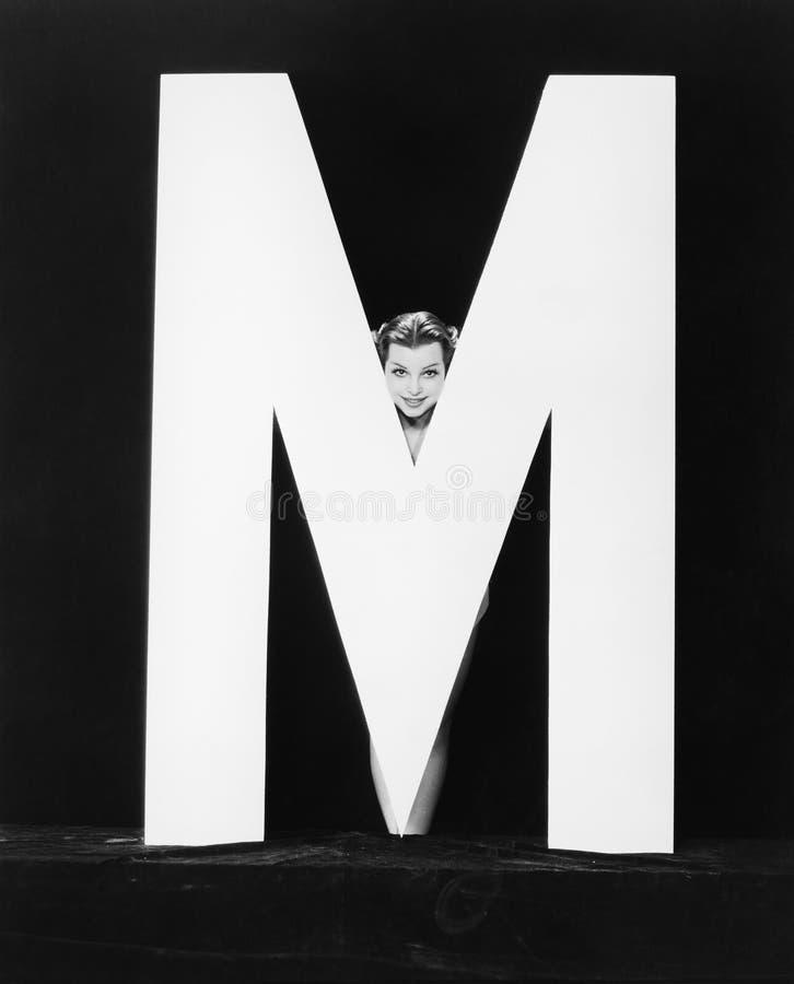 Kvinnas framsida med enorm bokstav M (alla visade personer inte är längre uppehälle, och inget gods finns Leverantörgarantier som royaltyfri foto