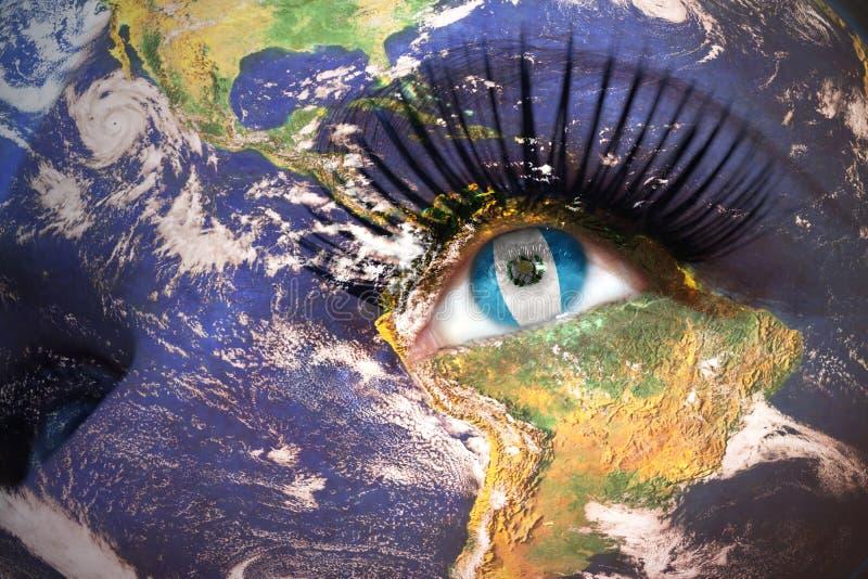 Kvinnas framsida med planetjordtextur och guatemalansk flagga inom ögat arkivfoto