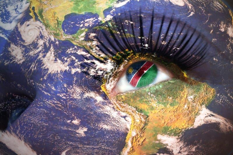 Kvinnas framsida med planetjordtextur och namibian flagga inom ögat royaltyfri foto