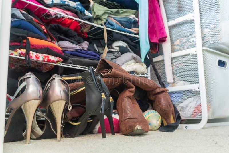 Kvinnas garderob med skor för hög häl, staplad vikt kläder på hyllor och delen av att hänga för ämbetsdräkter Visa hemli royaltyfria foton