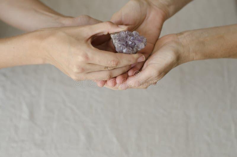 Kvinnas händer som ger en ametistkristall en till andra arkivbilder