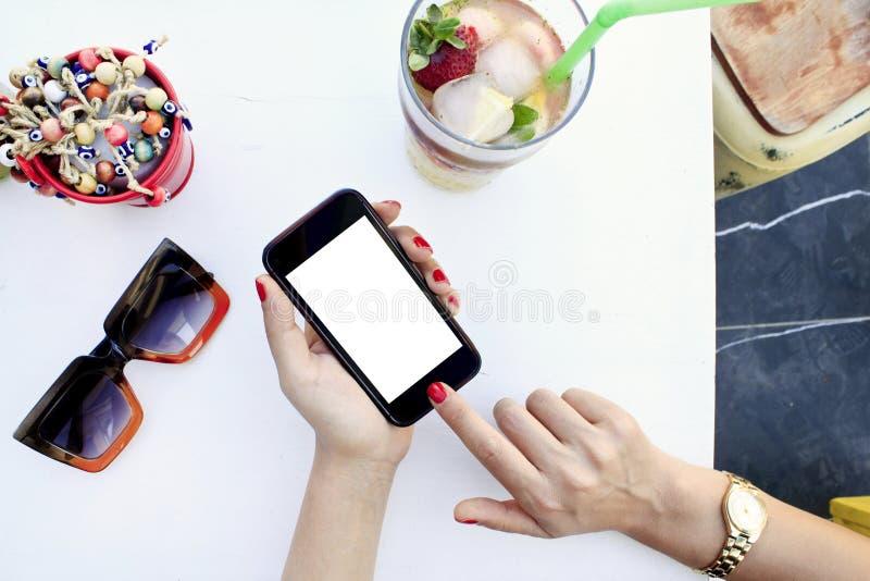 Kvinnas h?nder som rymmer den svarta mobiltelefonen med den tomma sk?rmen i kaf? royaltyfri bild