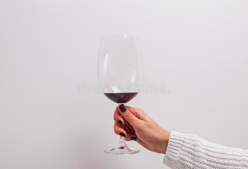 Kvinnas hand i en vit tröja som rymmer ett exponeringsglas av rött vin royaltyfria bilder