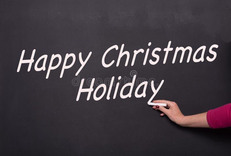 Kvinnas hand med krita på svart tavla som skriver lycklig jul arkivfoton