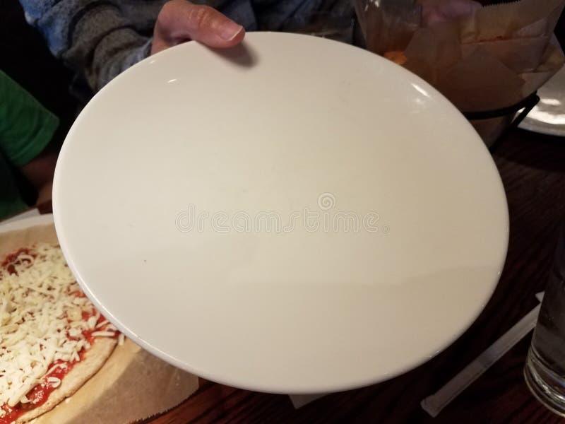 Kvinnas hand som rymmer den tomma vita plattan nära pizza fotografering för bildbyråer