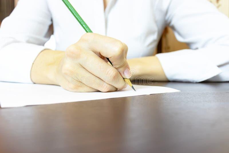 Kvinnas hand som skriver upp något på pappersslut Oigenkännlig affärskvinna i vit skjortahandstil med en blyertspenna royaltyfria foton