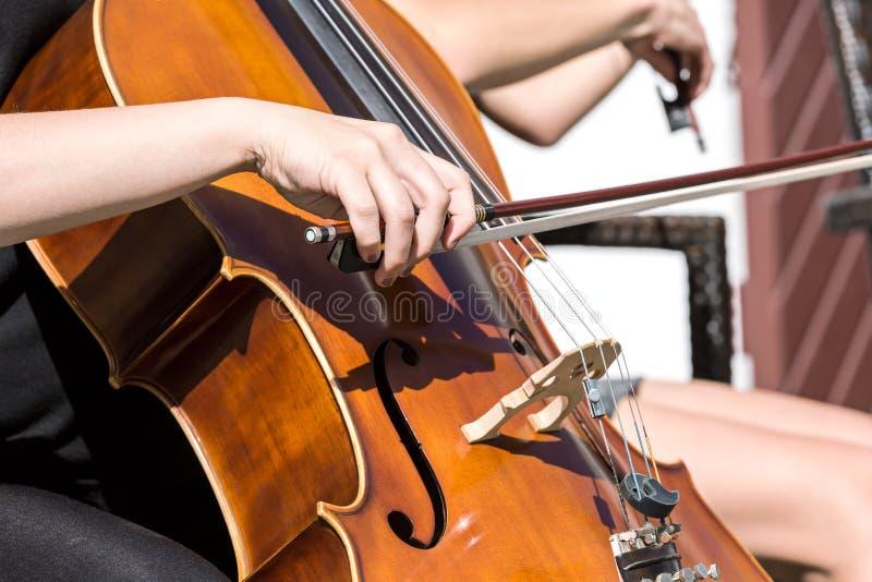 Kvinnas hand som spelar violoncellen i orkesteren arkivbilder