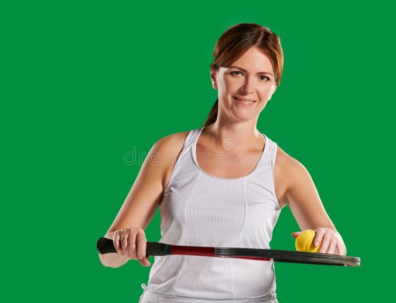 Kvinnas stående med en tennisracket och boll royaltyfri bild