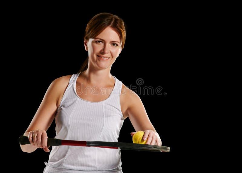 Kvinnas stående med en tennisracket och boll royaltyfria foton
