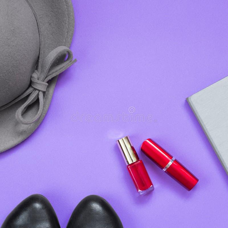 Kvinnas tillbehör, mobiltelefon, skönhetsmedel på ljus - violett bakgrund Kopiera utrymme för text arkivfoton
