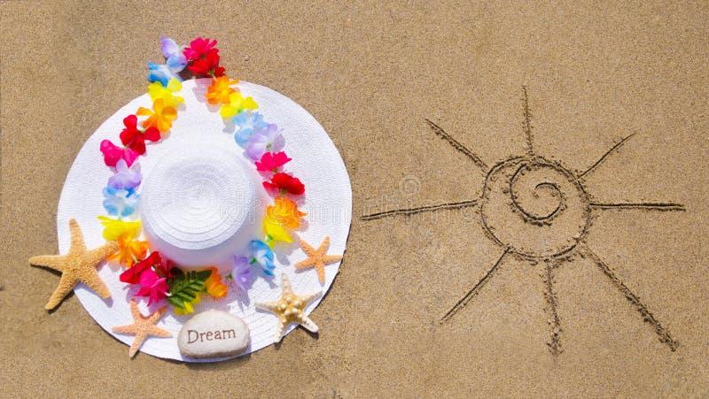Kvinnas vita hatt på den sandiga stranden royaltyfri fotografi