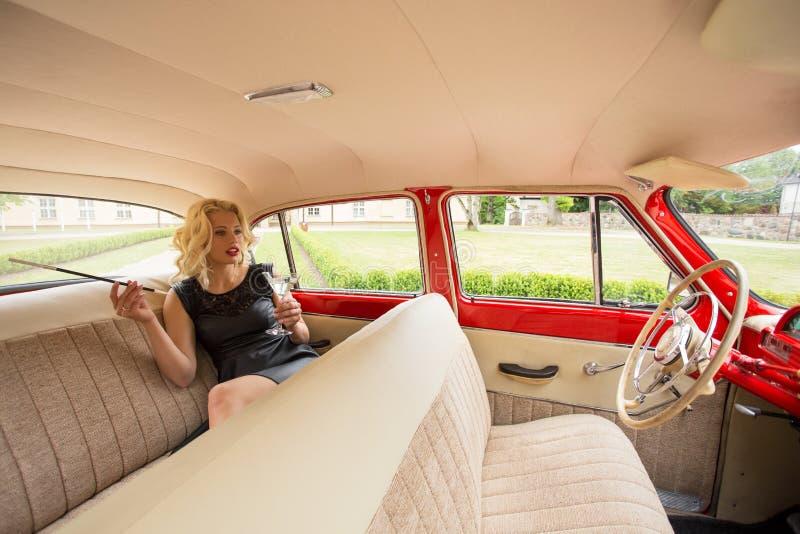 Kvinnasammanträde i backseaten av den retro bilen arkivbild