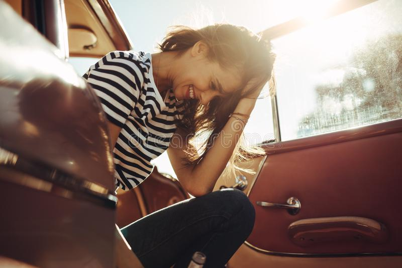 Kvinnasammanträde i bilen och skratta royaltyfri foto
