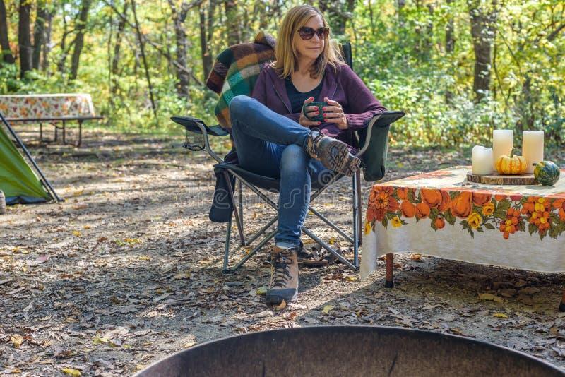 Kvinnasammanträde i campa stol med rånar av kaffe på campingplatsen royaltyfria bilder