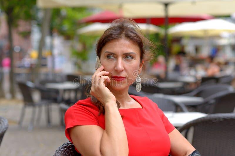 Kvinnasammanträde i ett kafé och ha en påringning royaltyfria foton