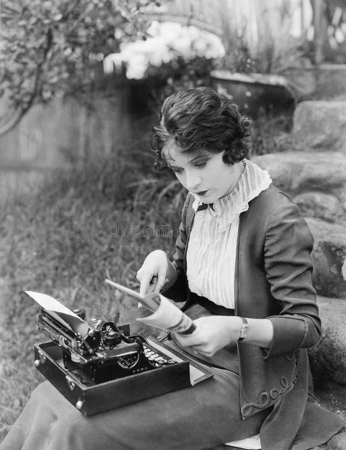Kvinnasammanträde i gården med en skrivmaskin på hennes varv (alla visade personer inte är längre uppehälle, och inget gods finns royaltyfri bild