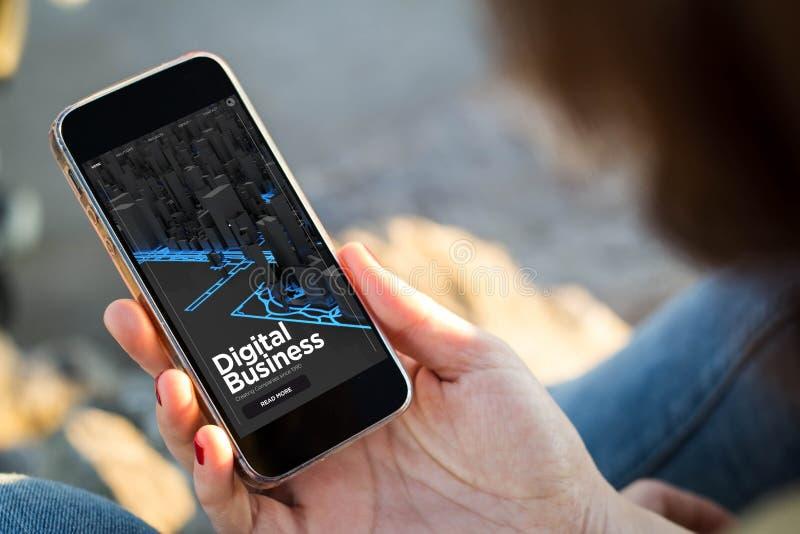 kvinnasammanträde i gatan som rymmer hennes smartphone som bläddrar digi royaltyfria foton