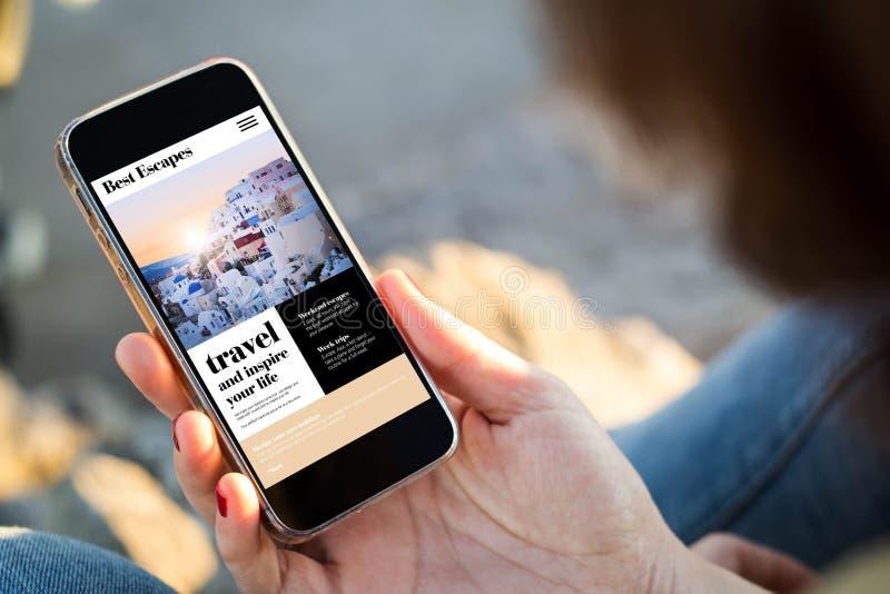 kvinnasammanträde i gatan som rymmer hennes smartphone för att resa onl arkivbilder