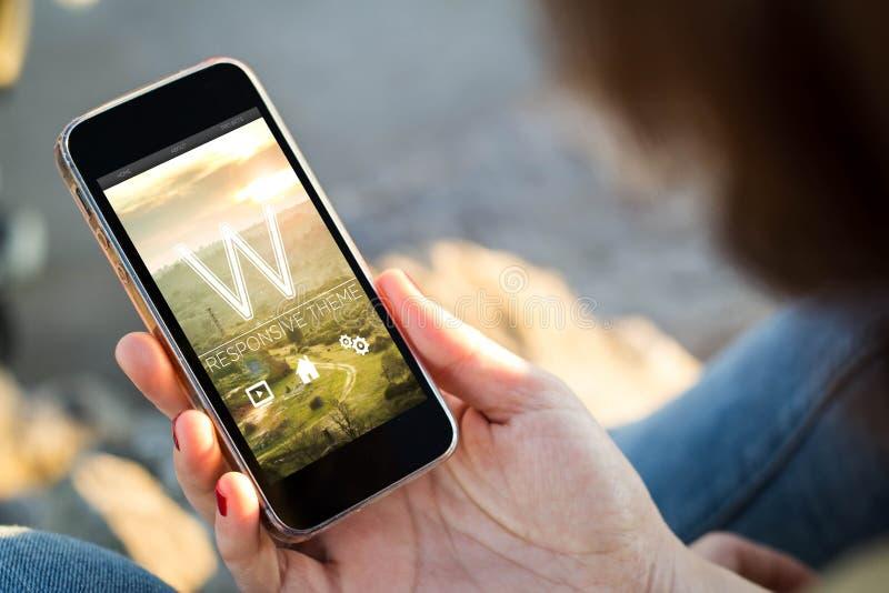 kvinnasammanträde i gatan som rymmer hennes smartphone med responsi royaltyfri fotografi