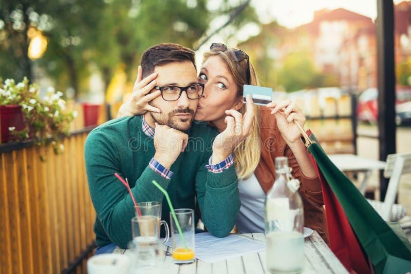 Kvinnasammanträde i kafé med den stiliga mannen och färgrika shoppingpåsar royaltyfri fotografi