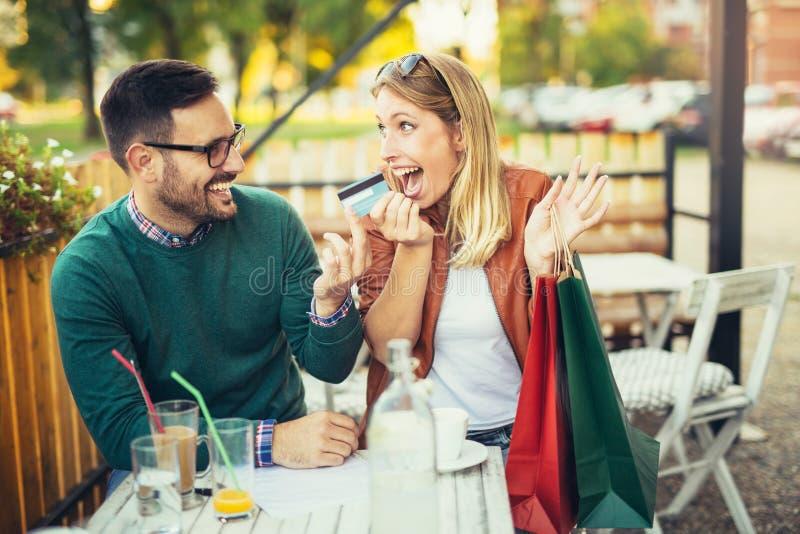 Kvinnasammanträde i kafé med den stiliga mannen och färgrika shoppingpåsar royaltyfri foto