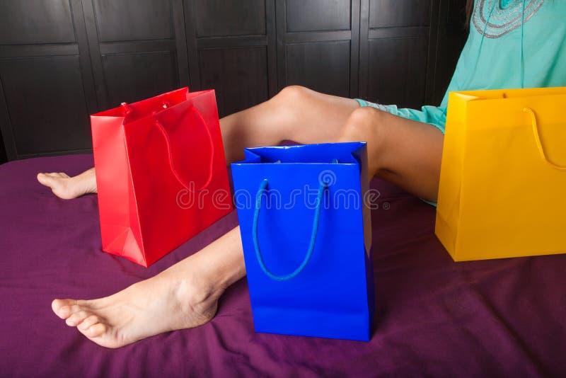 Kvinnasammanträde i säng med shoppingpåsar arkivfoto